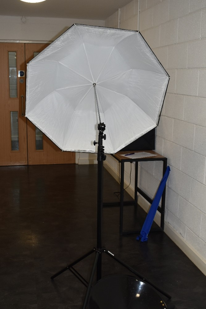 A selection of lighting equipment including a pair of Lastolite collapsable reflectors with tripod