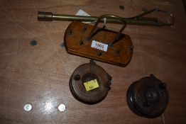 An assortment of antique fishing tackle including two wooden reels and an extending brass gaff.
