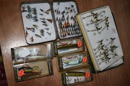 A collection of wooden and quill lures and a tin of flies.