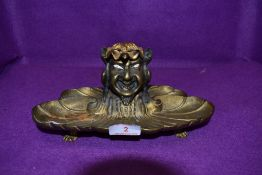 A late 19th/early 20th century gilded bronze gents desk top ink well having grotesque squatting