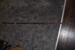 A tribal spear having solid wood shaft with wrought iron head and guards measuring 180cm long