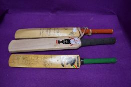 Three miniature cricket bats two bearing signatures one dated 1998 and similar