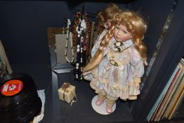 Two dolls with stands, a selection of necklaces and a mirrored photo frame.