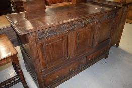 A period oak mule chest having carved frieze, three panel top section over double drawer base,