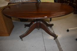 A late 19th century mahogany composite dining table having oval top on bulbous column and