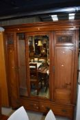 A Victorian mahogany double wardrobe having dentil cornice over mirrored centre panel flanked by
