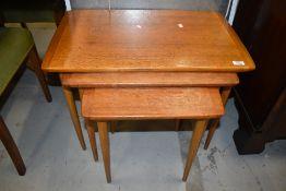 A vintage teak nest of three tables, on tapered legs