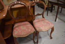 A pair of mahogany balloon back dining chairs, repair to backs