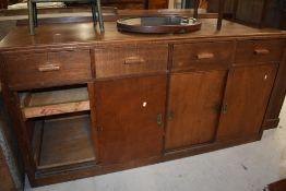 A vintage oak shop or office counter, having four frieze drawers over cupboard base having sliding