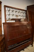 A late 19th/early 20th Century mahogany panelled bed frame, including side irons and base, width