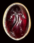 A ptolemaic garnet intaglio set in a gold ring. Cornucopia.