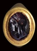 An fine hellenistic garnet intaglio mounted on an ancient gold ring. Bust of Isis.