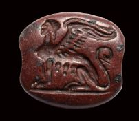 An archaic greek red jasper engraved seal. Seated sphinx.