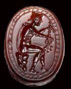 An etruscan carnelian scarab intaglio. Hermes with caduceus.