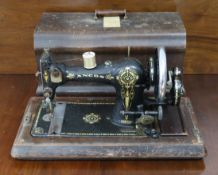 A Singer hand sewing machine in walnut dome-top case (decoration worn); & an Ancos ditto.