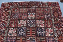 A Persian pattern carpet of crimson & deep blue ground, & with all-over repeating multi-coloured