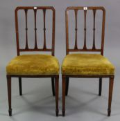 A pair of Edwardian satinwood – inlaid mahogany rail-back occasional chairs with padded seats & on