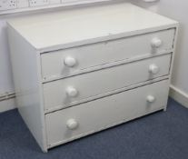 A white painted pine low chest, fitted three long graduated drawers with turned knob handles, 39""