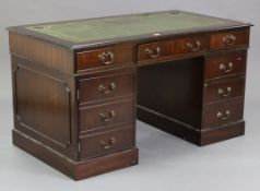 A reproduction mahogany pedestal desk inset gilt-tooled green leather, fitted two long drawers to