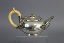 A George IV silver teapot of compressed round form, with ivory scroll handle & finial to the