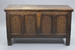 A late 17th century joined oak coffer, the four-panel front profusely carved with the tree of life