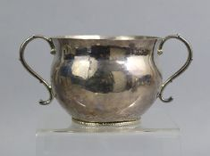 A COMMONWEALTH PERIOD SILVER PORRINGER of baluster form with two scroll handles, a chased narrow