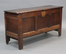 An 18th century oak coffer with hinged lift lid, three fielded panels to the front and on short