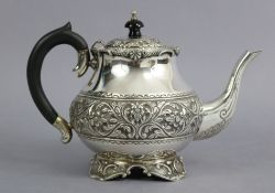 A continental white metal teapot of compressed round form, with hinged lid & repoussé bands of