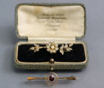 """A 9ct. gold propeller-shaped bar brooch set small ruby to the centre, 1¾"""" long; & a 9ct. gold flower"""