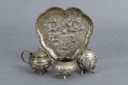 An eastern white metal three-piece condiment set on lobed heart-shaped tray, with repoussé