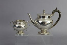 A George V silver teapot of ovoid form, with vase finial to the flat hinge lid, gadrooned rims, on