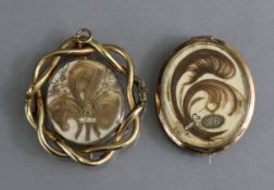 A Victorian yellow metal hollow-work oval brooch with entwined foliate border, the revolving