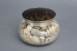 A large cut glass powder jar of squat round form, with removable silver-mounted tortoiseshell lid,