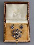 A 15ct. gold, Sapphire, & Diamond brooch/pendant of circular open-work design, the central flower-
