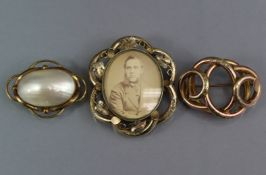 """A Victorian yellow metal hollow-work brooch on intertwined scroll form, 2"""" wide; a similar"""