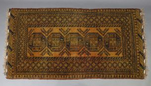 """An Afghan rug of orange & black ground & with five ghuls to centre within a multiple border, 80"""" x"""
