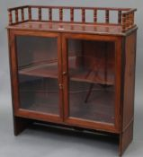 A Victorian mahogany small standing bookcase with spindle gallery to the top, & fitted centre