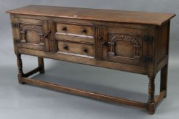 A GOOD QUALITY REPRODUCTION OAK SIDEBOARD fitted two long graduated drawers to centre flanked by