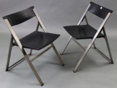A pair of silvered-metal & black plastic fold-away chairs after a design by Justus Kolburg.