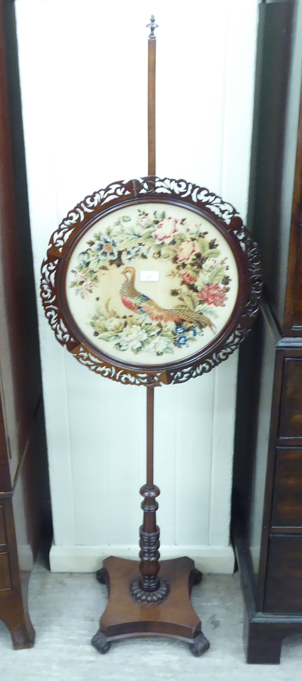 Lot 31 - A William IV mahogany polescreen, set with a peacock and floral embroidered panel,