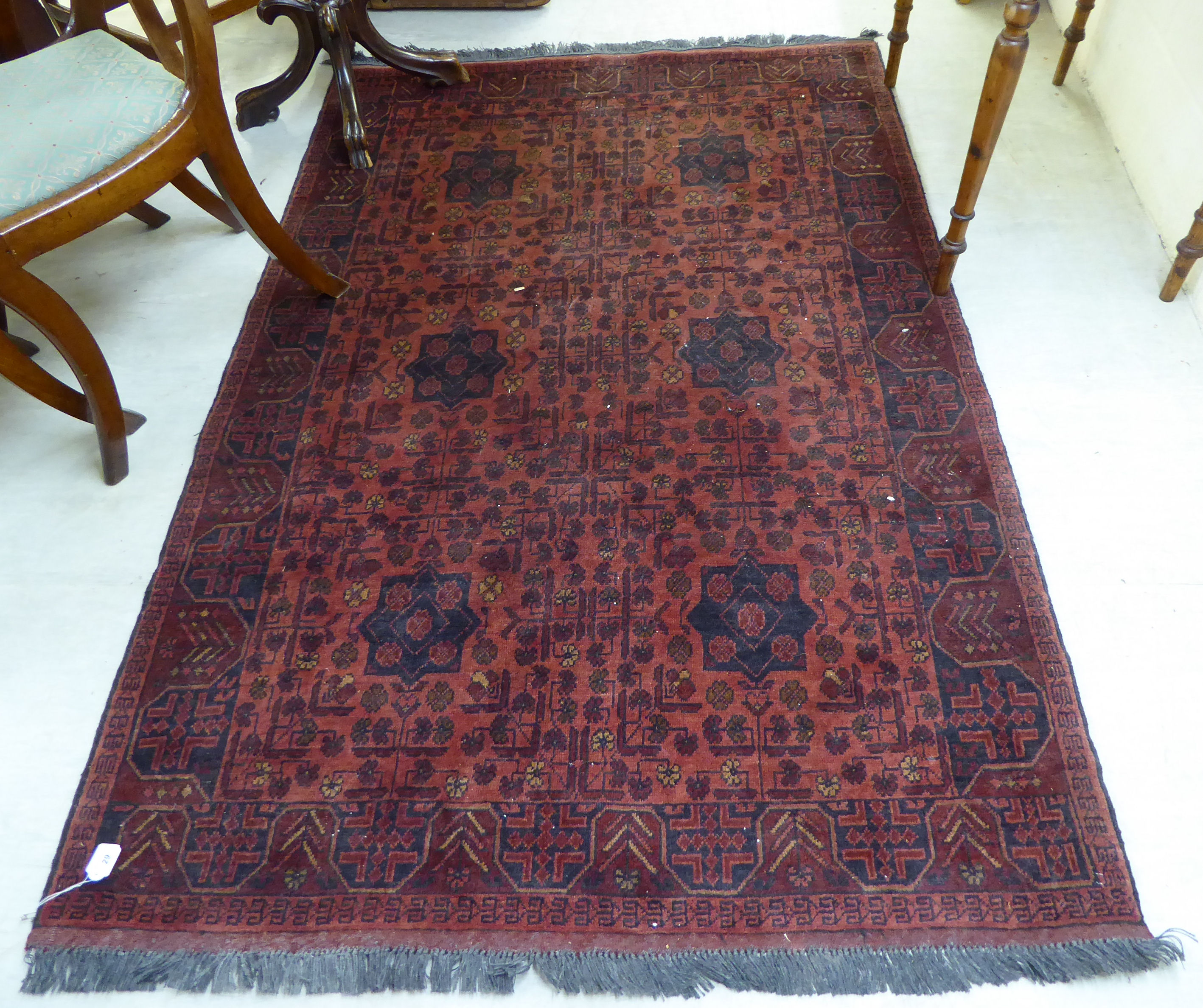 Lot 29 - A Persian design rug decorated with stylised floral designs on a red ground 50'' x 74'' BSR