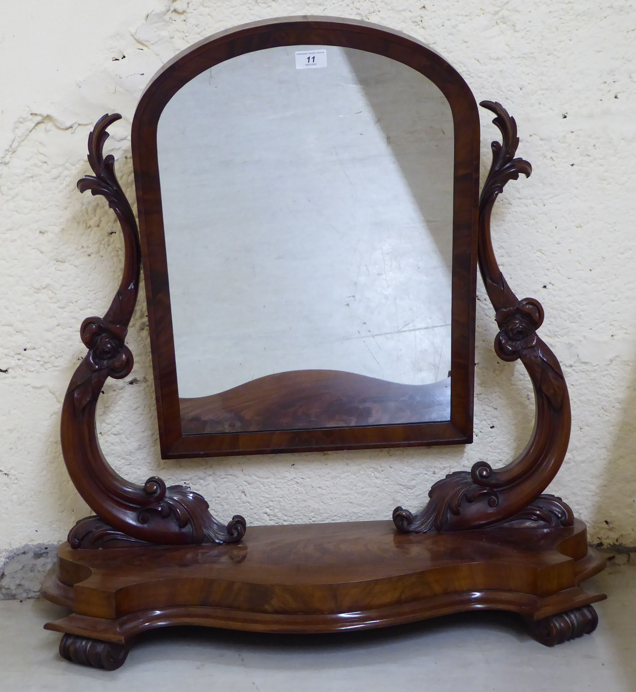 Lot 11 - A late Victorian mahogany dressing table mirror, the arched plate set between foliate moulded,