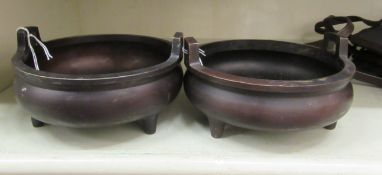 A pair of Oriental cast and patinated bronze censers, the shallow,