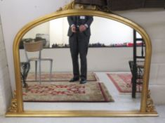 A modern round arched overmantel mirror,