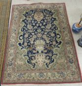 A Persian rug, decorated with a garden urn, birds and flora,