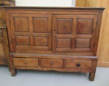 A George III oak chest with a pair of fielded panelled doors, over three in-line drawers,