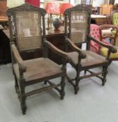 A pair of late 19thC baronial style, oak framed, high back chairs with carved crests, side pillars,