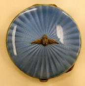 A silver circular powder compact with a hinged, radiating engine turned blue enamel lid,