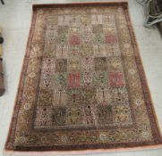 A Persian part silk/part woollen rug, decorated with repeating rectangular panels,