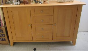 A modern beech sideboard with a central bank of five drawers, flanked by a pair of doors,